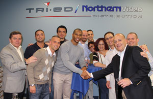 Victor Cruz shakes the hand of Tri-Ed / Northern Video President and CEO Pat Comunale