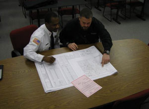 Two security personnel looking at papers