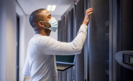 Man Wearing Mask Working on Security Server