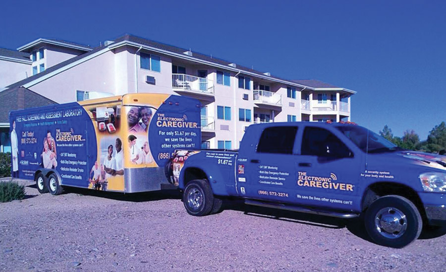 The Electronic Caregiverâ??s branded van is parked in the driveway of an apartment complex where employees will install a home monitoring device for a customer.