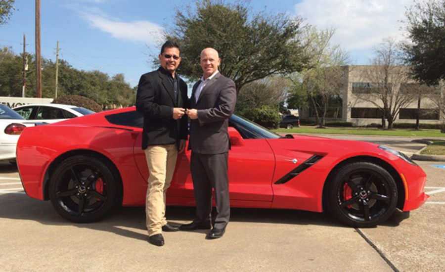 John Sullivan (right), senior vice president of sales at ADI, hands over the keys to a new Chevy Corvette to Ricky Gonzalez, owner of ACI Telephones in Houston, Texas.