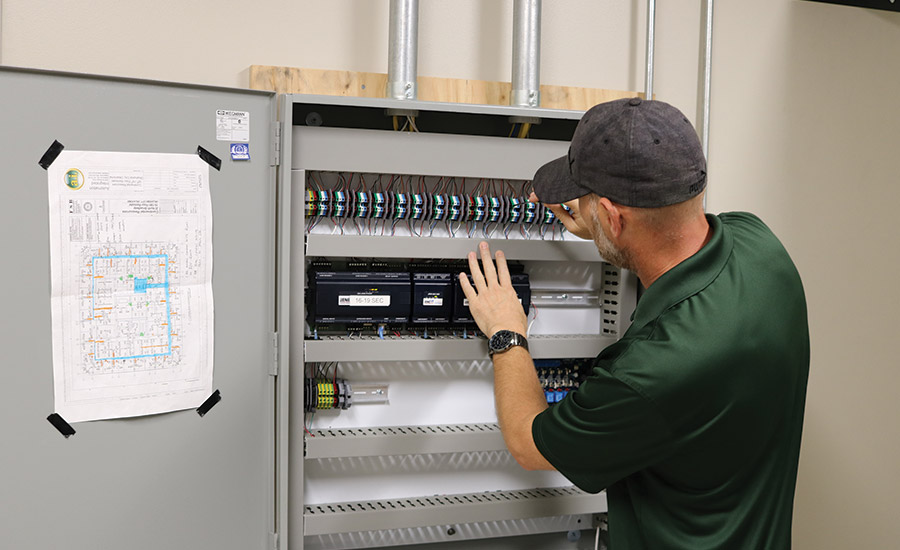 Automation Integrated Security Analyst Jason Arneson services an enterprise access control panel.